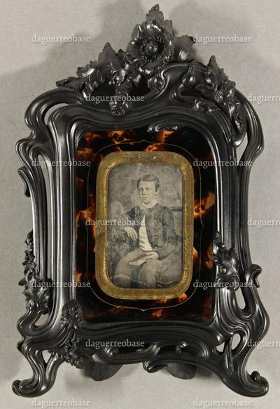 Junge in uniformähnlicher Jacke mit einem Buch in der Hand an einem Tisch sitzend, Dreiviertelfigur.