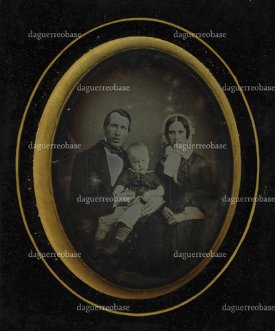 Family group portrait of a man, woman and a child, the child is sitting on th man's lap