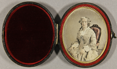 Frau mit grauen Haaren in einem Sessel leicht nach vorn gebeugt sitzend, Dreiviertelportrait, koloriert.