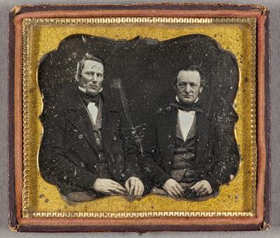 Puolikuvassa kaksi miestä, vanhempi ja nuorempi. Miehet ovat pukeutuneet samalla tavalla, tummat takit, liivi, valkoinen paita ja tumma huivi kaulassa. Miesten selän takaa erottuu koristeellisen sohvan tms. selkänoja.