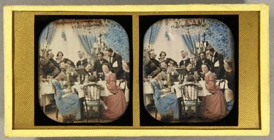 Gesellschaft um einen Tisch inszeniert, links spielt einer ein Seiteninstrument, ein anderer Mann hält eine Zeitungsrolle, einer bestellt bei einem am Tisch stehenden Kellner, eine Karte in der Hand haltend, eine Frau hat sich zum Fotografen gedreht, ein Mädchen sitzt ihr etwas gelangweilt gegenüber, vor ihrem Stuhl hockt eine Katze, koloriert.