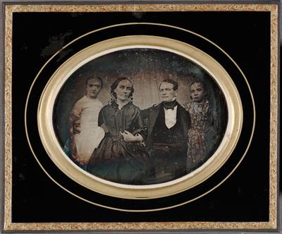 Group portrait, Town council Johan Felen with family. Ryhmämuotokuva, Kristiinankaupungin raatimies Johan Felen (1812-1879) ja puolisonsa Anna Helena os. Lacke (1805-1866) tyttärineen. Kuva on otettu ehkä Kristiinankaupungissa tai Raahessa. Mustassa, kultareunaisessa kehyksessä on soikea, vaakasuuntainen kuva-aukko. Raatimies, vaimo ja kaksi kouluikäistä tytärtä ovat asettuneet riviin siten, että mies (oikealla) ja vaimo (vasemmalla) istuvat keskellä, tyttäret seisovat sivuilla heidän vieressään. Taustalla näkyy vaalea, hieman poimuileva verho. Kaikki neljä henkilöä katsovat suoraan kohti vakavina mutta hyväntuulisen näköisinä, kasvot hieman sivulle käännettyinä. Mies on kietonut toisen kätensä vieressään olevan tytön vyötäisille ja ojentanut toisen vaimonsa tuolin selkämykselle; vaimo on kietonut myös toisen kätensä vieressään olevan tytön vyötäisille, ja toinen käsi koukistuu syliin kuin pidellen jotakin. Vasemmanpuoleisella tytöllä on valkoinen, lyhythihainen leninki, jossa on tyköistuva yläosa ja leveä hameosa. Hänen kasvonsa näkyvät hieman muita epätarkempina. Oikeanpuoleisella tytöllä on kuviollinen, pitkähihainen leninki. Raatimiehen puolisolla on tumma, väljä, vyöllinen silkki- tai taftileninki, jonka hihansuista ja kauluksesta näkyy valkoista. Hänellä on takaraivolla pieni päähine, josta näkyvissä ovat lähinnä niskaan riippuvat, tummista pyöreistä levyistä helminauhamaisesti muodostetut koristenauhat. Raatimies on paljain päin, hiukset sivujakauksella, ja hänellä on tummat housut, liivit, avoin tumma takki, valkoinen paita ja kaulassa rusetille solmittu huivi. Äidin ja tytärten hiukset on kiinnitetty taakse tiukalla keskijakauksella.