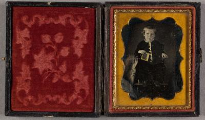 Portrait of a child sitting in a rocking chair. Kokokuva  lapsesta, pojasta, joka istuu lasten keinutuolissa.  Pojan vasemmassa kädessä on kulmikas esine, mahdollisesti kirja. Pojalla on yllään tumma asuste, jossa on  pitsisomisteita, sekä nahkakengät. Pojan takin napitusta sekä kädessä olevaa esinettä on korostettu kömpelöllä kultavärityksellä, asun pitsikoristeita on myös korostettu valkoisella. Pojan poskissa on punaista väriä.