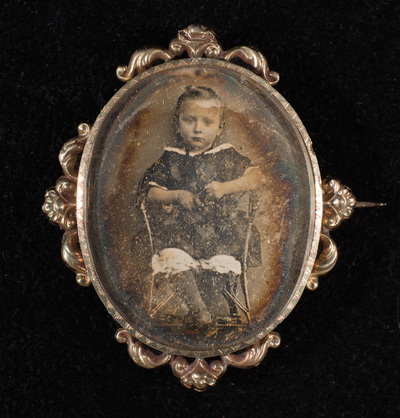 Portrait of a child,  three-quarter lenght, sitting on a chair. Beautiful small brooch with glass, plate and frame. Pin with tube hinge and C catch.