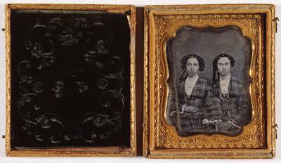 Portrait of  two young girls in similar checkered dresses, possibly sisters. Puolikuvassa kaksi nuorta naista, mahdollisesti sisarukset, jotka ovat pukeutuneet samanlaisiin ruudullisiin asusteisiin.