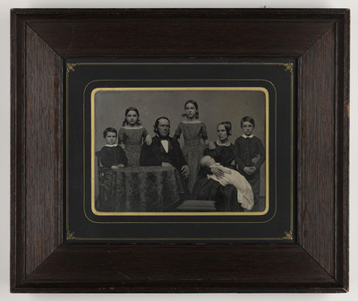 Portrait of seven people: child, child, man, child, woman, baby and child