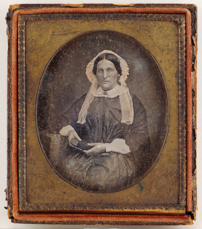 Portrait of an middle-aged woman with a book. She has a white lace bonnet. Puolikuvassa keski-ikäinen nainen kirja sylissään. Naisella on päässä valkoinen pitsihilkka.