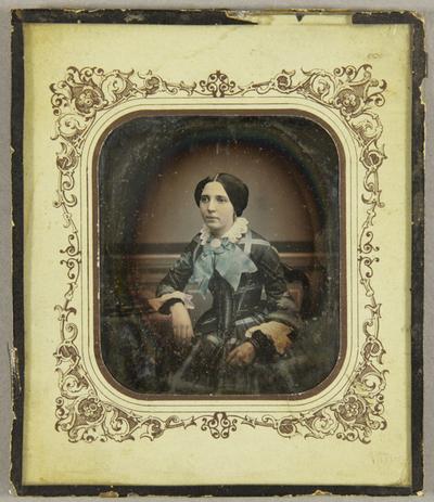 Junge Frau seitlich an einem Tisch sitzend, ein Arm darauf ruhend vor einer gemalten Landschaftskulisse, Dreiviertel, koloriert.