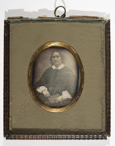 Portrett av ukjent kvinne sittende med en bok i fanget.  Portrait of unknown woman seated with a book in her lap.
