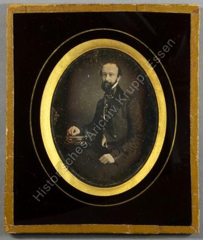 Alfred Krupp seitlich an einem Tisch sitzend, auf dem sein Unterarm ruht