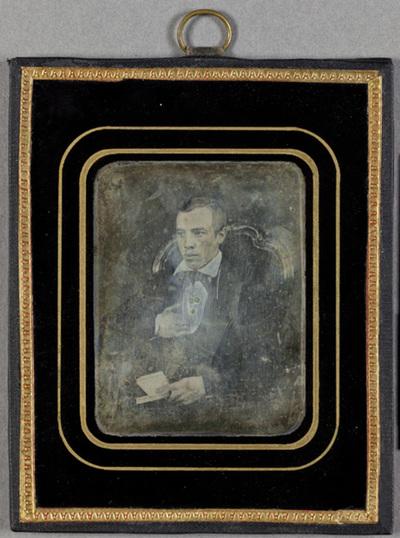 Portrait of a man with a book, sitting on a chair with a book. Puolikuvassa nuorehko mies, joka istuu tuolilla. Miehen vasen käsi on taivutettu puvun takin liepeen alle. Oikea käsi on sylissä, ja siinä on kirja.