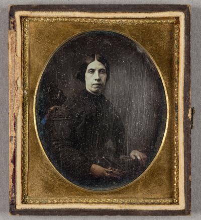 Puolikuvassa nainen istuu korkeaselkäisellä tuolilla, vasemmassa kädessä on kirja.