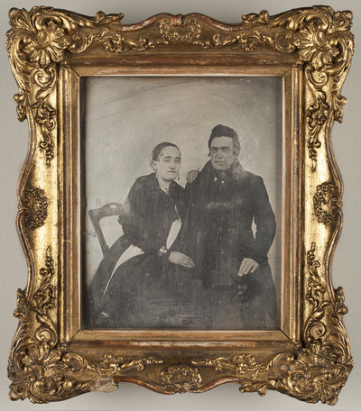 Portrait of a couple, seated. Woman is resting her left hand on man´s shoulder