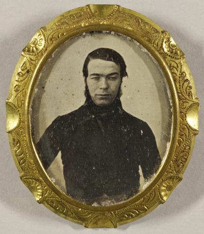 Junger Mann mit Backenbart, dunkel gekleidet, Halbfigur.