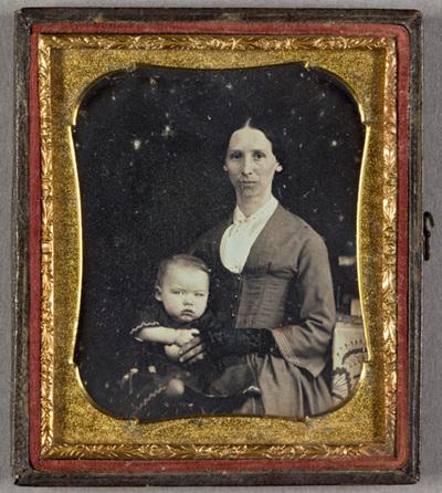 Portrait of a woman with a child. Puolikuvassa  lapsi ja nainen. Lapsi on naisen sylissä. Lapsi katsoo kameraan, lapsella on yllään tumma   Naisella on yllään hame ja keskivartalosta tyköistuva takki. Lapsella on tumma pitsikirjailtu asu.