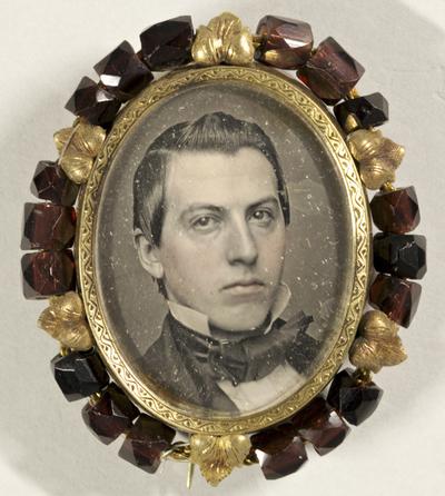 Brustportrait eines jungen Mannes, leicht koloriert, in einer Brosche mit einem Kranz aus kleinen Granatsteinen und vergoldeten Metallblättern.