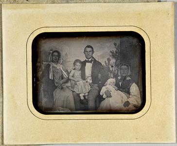 Ehepaar mit ihren beiden Kindern, ein Kind hält die Kinderfrau auf dem Arm vor der Kulisse Lübecks sitzend.