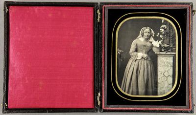 Ältere Dame steht an einer Säule mit einer Blumendekoration, Dreiviertel