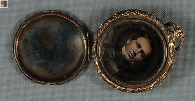 Two round plates housed in a pocket watch locket with bevelled christals. Both images show severe tarnish