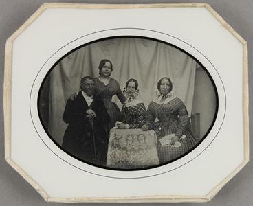 Familienbild mit vier Personen, drei Frauen und ein Mann um einen Tisch stehend. Im Hintergrund ein weißer Vorhang.