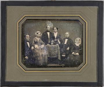 Familienbild mit 6 Personen, in der Mitte ein Tisch stehend hinter dem ein Mann und eine Frau stehen, die anderen Paare sitzen rechts und links daneben.