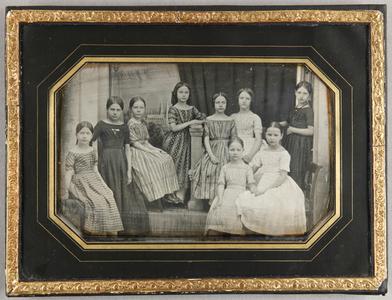 Gruppenaufnahme mit 9 Mädchen im Atelier sitzend und stehend, Ganzfigur. Im Hintergrund ein Vorhang in der rechten Bildhälfte, links davon eine gemalte Stadtansicht Lübecks mit Marienkirche.