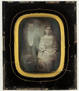 Portrait of a young couple. Puolikuva nuoresta pariskunnasta. Miehellä on yllään puvuntakki, ruudulliset housut ja liivi. Naisella on mekko, ja medaljonki kaulassa.
