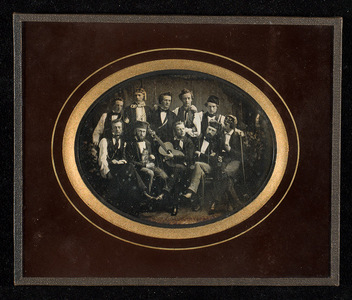 Group portrait of ten young men. Five seated in front. The second on the left holding a cat, the one in the middle holding a guitar. Some of them wearing the same ribbons as in GBB-S378.
