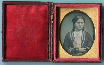 Woman with red scarf and brooch.