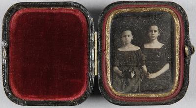 Zwei junge Mädchen in schulterfreien Kleidern, ein Mädchen hält ein aufgeschlagenes Buch in einer Hand, mit der anderen hält sie die Hand der Schwester.