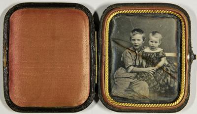 Zwei Kinder, Geschwister, der ältere Bruder hält seine jüngere Schwester im Arm, sitzend, Dreiviertel.