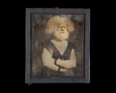 Ett i en serie (NTM 4311) på 24 daguerreotypier fra fotograf Severin Worm-Petersen innkommet i 1936. Innrammingen er ikke original (kan stamme fra Norsk Teknisk Museum eller andre). Feil museumsnummer skrevet på baksiden.  Mannen er trolig Rudolph Lucasie som ble oppdaget av P.T. Barnum på et marked i Amsterdam. Fra 1857 til sin død i 1898 var han berømt som en del av Albinofamilien fra Madagaskar ved Barnums sirkus i New York. /  One of 24 daguerreotypes (NTM 4311) accessed from the photographer Severin Worm-Petersen in 1936. Framing not original (could be by Norwegian Museum of Science and Technology or other). Wrong museum number written on the backside. The man is probably Rudolph Lucasie, discovered by P.T. Barnum on an Amsterdam market place. From 1857 onwards he became famous as a member of The Albino family from Madagascar at Barnum's circus in New York.