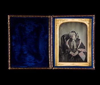 """Bildet er en del av en serie som består av to miniatyrmalerier, to daguerreotypier og 8 ambrotypier om Miss Hogg's familie. En lapp med teksten """"Miss Hogg's Grandmother 14/8-1931"""" ligger ved bildet, trolig skrevet av en tidligere eier. Håndkolorerte hudtoner og sjal./ The picture is from a series consisting of two miniature paintings, two daguerreotypes and 8 ambrotypes. Texted """"Miss Hogg's Grandmother 14/8-1931"""", probably by former owner. Hand colored skin colour and shawl."""