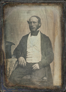 Portrait of a man sitting on a chair, on the left side a top hat on the table.