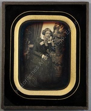 Bertha Eichhoff an einem mit gemustertem Tuch bedeckten Tisch sitzend, auf dem eine Pflanze steht, die Hand melancholisch an das Kinn gelegt, Ganzportrait.