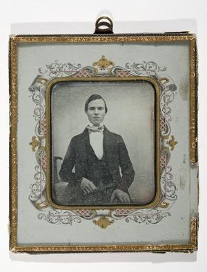 Portrett av ukjent mann sittende med en arm hvilende på et bord. Flosshatten ligger på bordet.  Portrait of unknown man seated with one arm resting on a table. A top hat on the table next to him.