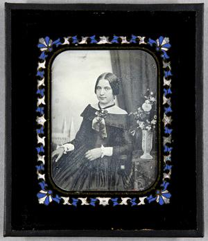 Junge Frau seitlich neben einem Tisch mit Blumenvase sitzend