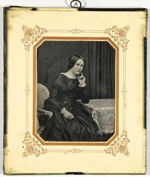 Junge Frau am Tisch sitzend, einen Arm aufgestützt, die Hand an die Wange gelegt, Dreiviertel