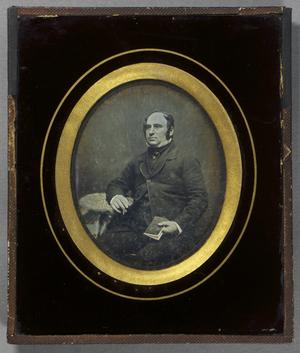 Ein seitlich am Tisch sitzender Mann mit einem Stift und einem Heft in den Händen, Dreiviertelportrait.