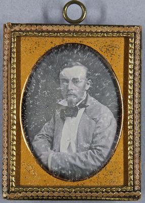 Junger Mann mit Schnurr- und Kinnbart in hellem Anzug mit duklem Binder, sitzend, Halbportrait.