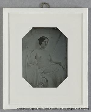 Modèle féminin, nu, à mi-corps, bras sur les accoudoirs