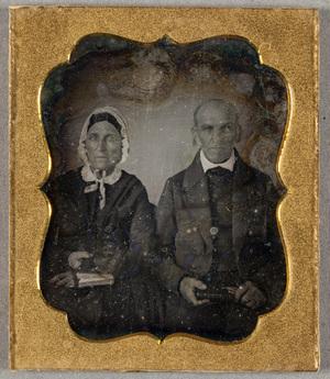Puolikuvassa keski-ikäinen pariskunta, molemmilla on kirjat kädessä, ja miehellä lisäksi silmälasit. Naisella on pitsireunainen hilkka päässä.