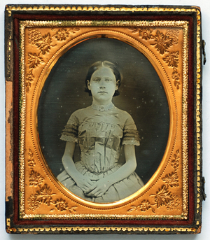 Three quarter length portrait of a seated girl. She wears a striped short sleeved dress, edged with white lace and a white lace collar with a central brooch. Her hands rest together on her lap. The image has a plain dark background.