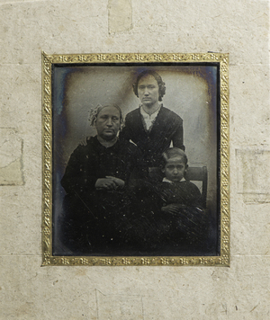 Three quarter length portrait of a family: Estonian writer Friedrich Reinhold Kreutzwald's wife Marie Elisabeth (1805-1888, former Saedler) and their two children, daughter Adelheid Anette (1834-1896, later Blumberg) and son Friedrich Alexis (1845-1910). The woman is sitting to the left, wearing a dark long sleeved dress, a pale lace-edged bonnet and a wedding ring. Her hands rest in her lap together. Her daugther is standing behind to her left, resting her hand on mother's right shoulder. She wears a dark long sleeved dress and a thin chain around her neck. The boy is sitting on a wooden chair to the right, resting his hands in his lap together. He wears a dark jacket and white collar is visible beneath the jacket. Part of the wooden back of his chair is also visible. The image has a plain background.
