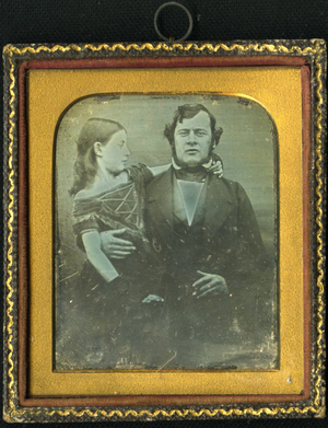 Double portrait of man in frontal pose, in formal dress with adolescent in short sleeves dress seated on his knees with her right arm around his neck. He holds her by the waist.