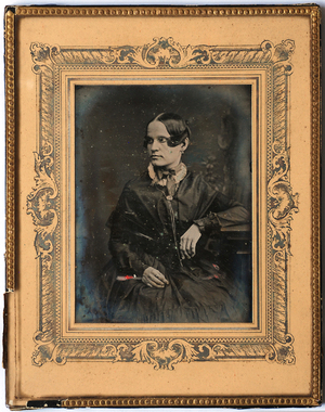 Three quarter length portrait of a seated woman, facing slightly to her right. She is resting her left arm on the table to her left and right hand on her lap. She wears a dark long sleeved dress with white lace collar and a broad ribbon tied in a bow around her collar. She also wears two rings on her fingers, earrings and a fine, long chain around her neck. There is a painted background.