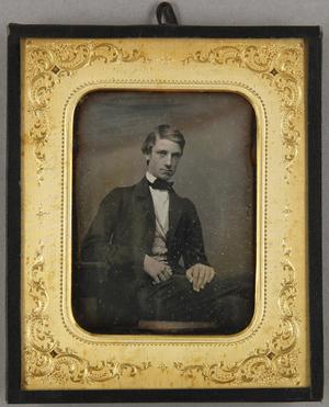 Junger Mann, am Tisch sitzend, hat unter seinem Jacket die Schärpe einer Verbindung umgehängt, Dreiviertel.