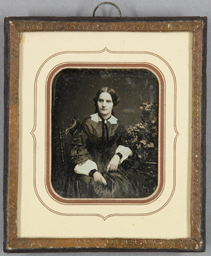 Frau an einem Tisch mit üppigem Blumengesteck sitzend, Dreiviertelportrait, koloriert.