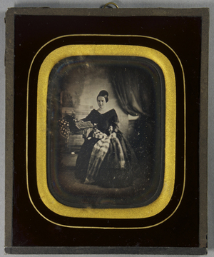Sitzende junge Frau, ein kariertes Schultertuch um die Hüfte gelegt, mit einem Buch in der Hand vor einer gemalten Kulisse und rechts einem Vorhang.