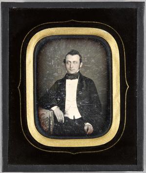Junger Mann am Tisch sitzend, ein Arm darauf ruhend, Halbfigur, teilkoloriert.
